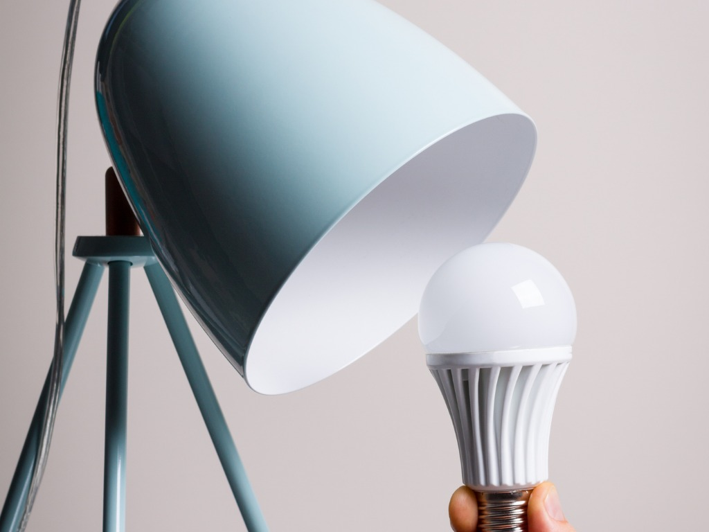 changing-the-bulb-for-led-bulb-in-table-lamp-in-turquoise-colours-picture-id848061646